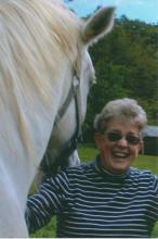 Susan Boardman on the farm with white horse